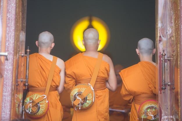 3 mnichów stojących w modlitwie w kościele
