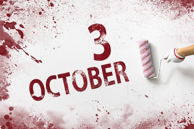 3 października. dzień 3 miesiąca, data kalendarzowa. ręka trzyma wałek z czerwoną farbą i pisze datę w kalendarzu na białym tle. jesienny miesiąc, koncepcja dnia roku.
