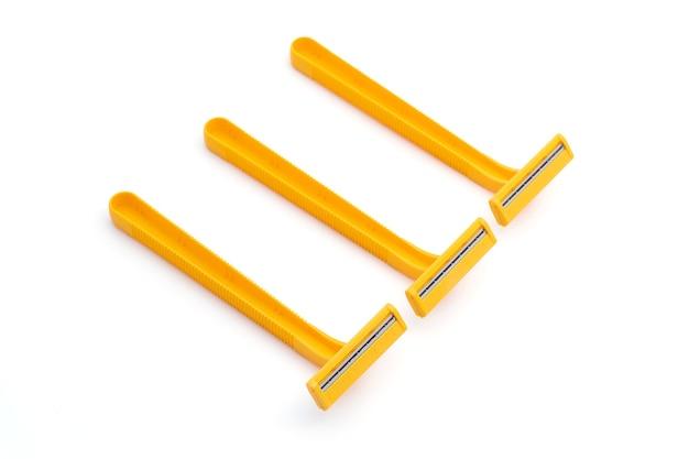 3 podwójne ostrza żółte jednorazowe maszynki do golenia na białym tle na białym tle.