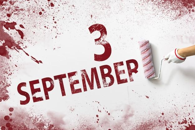 3 września. dzień 3 miesiąca, data kalendarzowa. ręka trzyma wałek z czerwoną farbą i pisze datę w kalendarzu na białym tle. jesienny miesiąc, koncepcja dnia roku.