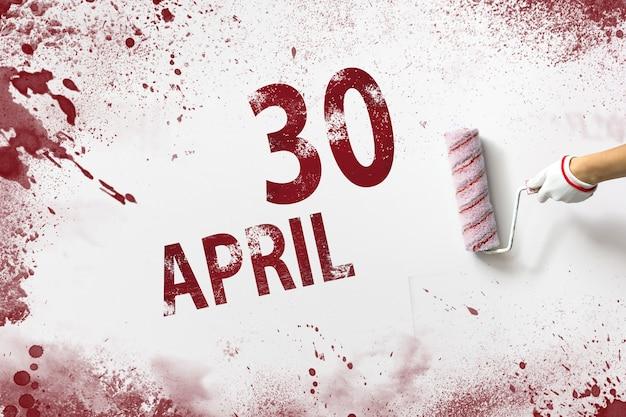 30 kwietnia. 30 dzień miesiąca, data kalendarzowa. ręka trzyma wałek z czerwoną farbą i pisze datę w kalendarzu na białym tle. miesiąc wiosny, koncepcja dnia roku.