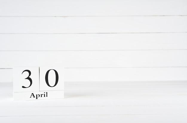 30 kwietnia, dzień 30 miesiąca, urodziny, rocznica, drewniany kalendarz blokowy na białym drewnianym tle z kopią miejsca na tekst.