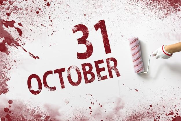 31 października. 31 dzień miesiąca, data kalendarzowa. ręka trzyma wałek z czerwoną farbą i pisze datę w kalendarzu na białym tle. jesienny miesiąc, koncepcja dnia roku.