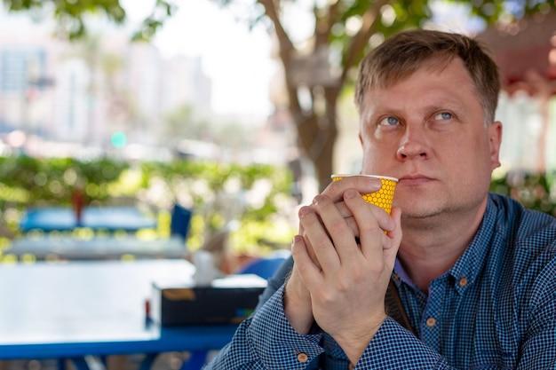 35-40-letni mężczyzna jest samotnym smutnym mężczyzną siedzącym ze szklanką kawy w ulicznej kawiarni.