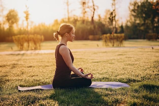36-letnia młoda kaukaska kobieta ćwiczy jogę wczesnym słonecznym porankiem na trawie z rosą miękka selektywna ostrość.