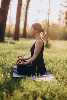 36-letnia młoda kobieta ćwiczy jogę rano w lesie wśród drzew w pozycji lotosu. miękka selektywna ostrość.