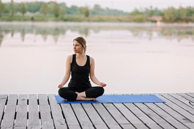 36-letnia młoda kobieta rasy kaukaskiej rano ćwiczy jogę w pozycji lotosu na świeżym powietrzu w pobliżu rzeki na drewnianym molo
