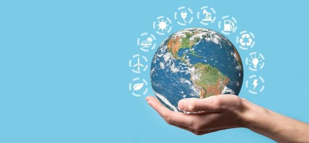 3d kula ziemska planety w ręce mężczyzny, kobiety, ręce na niebieskim tle.