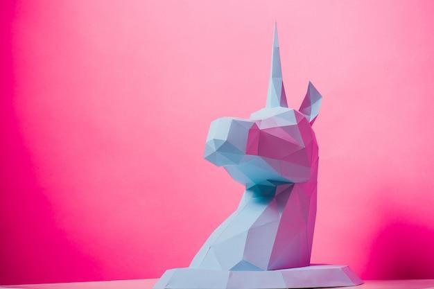 3d papierowa jednorożec na różowym tło lewej stronie, horyzontalna. zabawka origami. origami pegaz