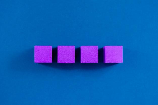 4 fioletowe drewniane klocki umieszczone w rzędzie, z miejscem do kopiowania, nad niebieskim miejscem.