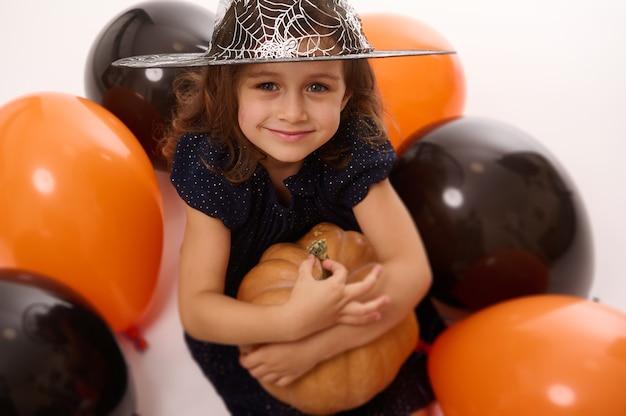 4-letnia dziewczynka w stroju czarownicy i kapeluszu czarodzieja bawi się balonami i dynią na białym tle. koncepcja dziecka bawiącego się na imprezie halloween