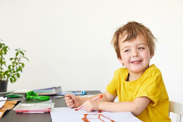 4-letnie dziecko ładny chłopiec rysuje przy stole i patrzy w kamerę na białym
