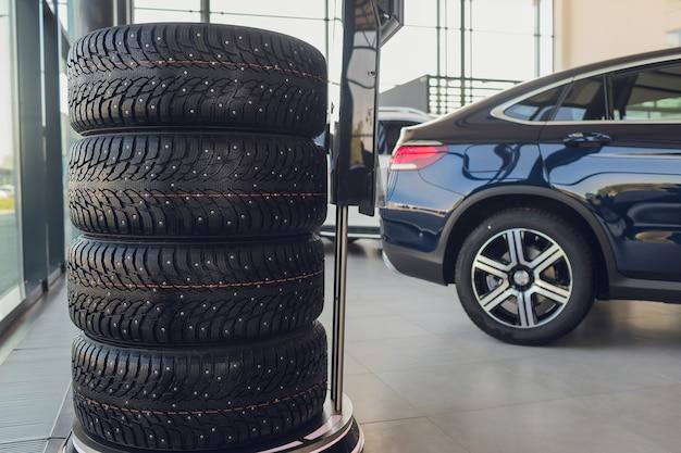 4 nowe opony, które zmieniają opony w warsztacie samochodowym, rozmyte tło