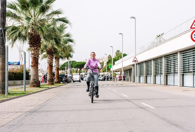 40-letnia kobieta jadąca na rowerze elektrycznym ulicami miasta (koncepcja mobilności elektrycznej)