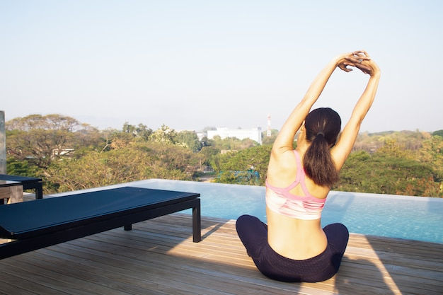 40s kobieta robi joga w pobliżu basenu na dachu. pojęcie zdrowego stylu życia