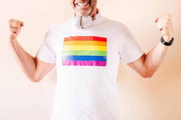 45-letni mężczyzna ubrany w białą koszulkę z flagą z dumą