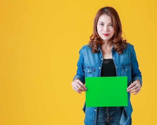 45s śliczne piękne kręcone włosy asian kobieta trzyma zielony karton pustego papieru, studio strzał z lampą błyskową na jasnożółtym tle. dodano pomysł na treści reklamowe.