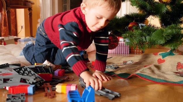 4k nagrania małego chłopca grającego na podłodze z kolejką pod choinką w godzinach porannych. dziecko otrzymujące prezenty i prezenty na ferie zimowe i uroczystości