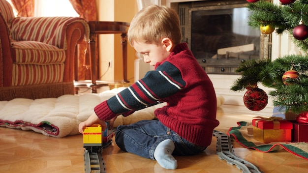 4k nagrania małego chłopca malucha budynku pociągu zabawki i kolei z cegieł i bloków pod choinką. dziecko odbiera prezenty i prezenty od świętego mikołaja podczas ferii i uroczystości zimowych