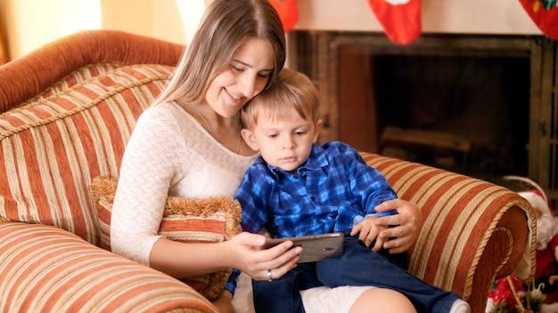 4k nagrania małego chłopca z matką relaks w dużym fotelu i oglądanie bajek na smartfonie. rodzina dobrze się bawi i bawi podczas ferii zimowych i uroczystości.