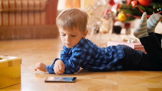 4k nagrania ślicznego małego chłopca leżącego na podłodze obok choinki i oglądania bajek na smartfonie. dziecko dobrze się bawi i bawi podczas ferii zimowych i uroczystości.
