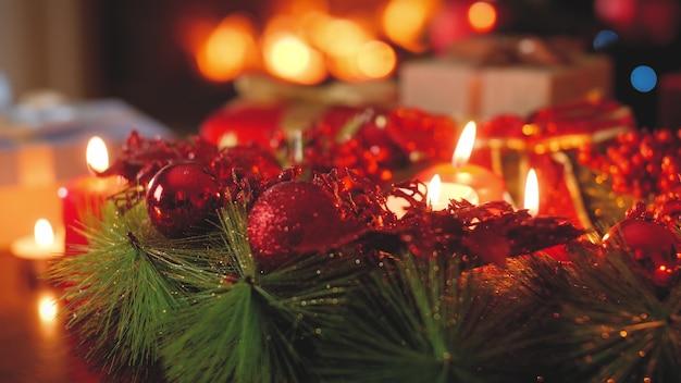 4k stonowanych nagrań płonących świec, wieńca adwentowego i prezentów świątecznych przeciwko palącemu się ogniu w kominku w salonie