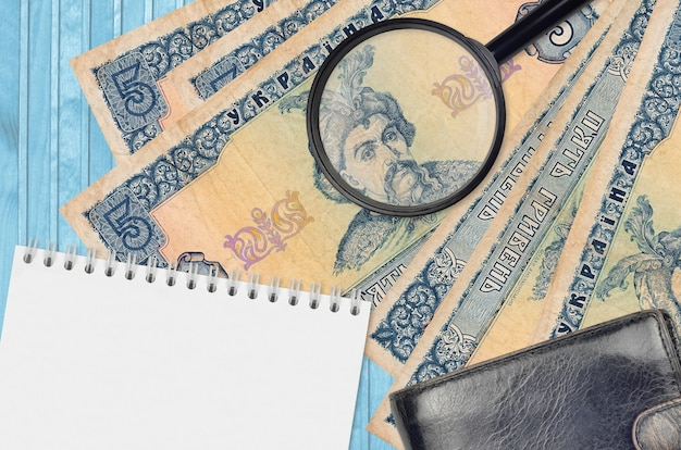 5 banknotów hrywny ukraińskiej i szkło powiększające, czarna torebka i notes