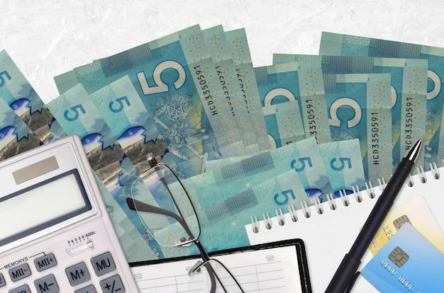 5 dolarów kanadyjskich rachunki i kalkulator z okularami i długopisem.
