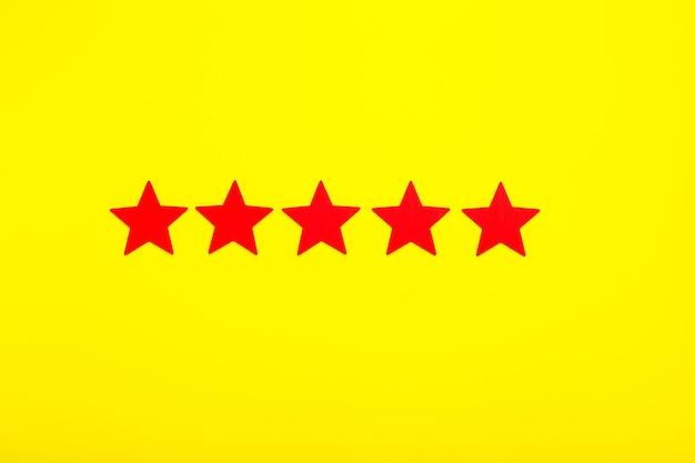 5 gwiazdek zwiększa ocenę, koncepcja customer experience. 5 czerwonych gwiazdek doskonała ocena na żółtym tle.