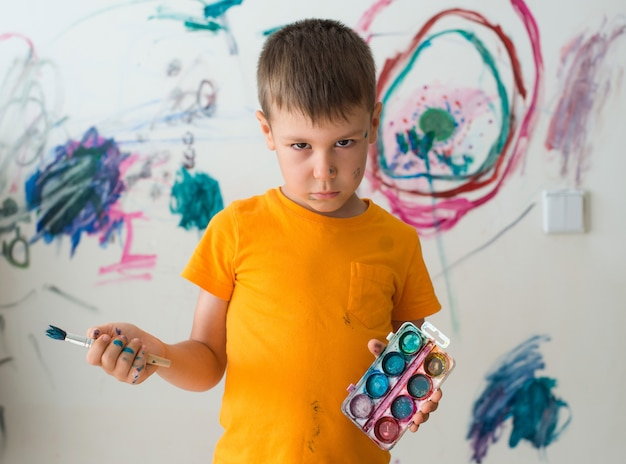 5-letni chłopiec o poczuciu winy, pomalowany farbą i pędzlem na ścianie swojego pokoju.