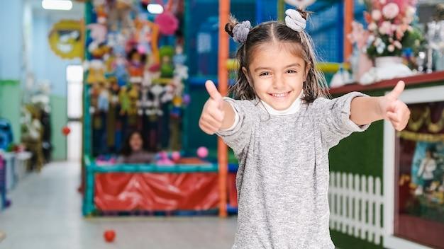 5-letnia dziewczynka uśmiecha się na placu zabaw dla dzieci