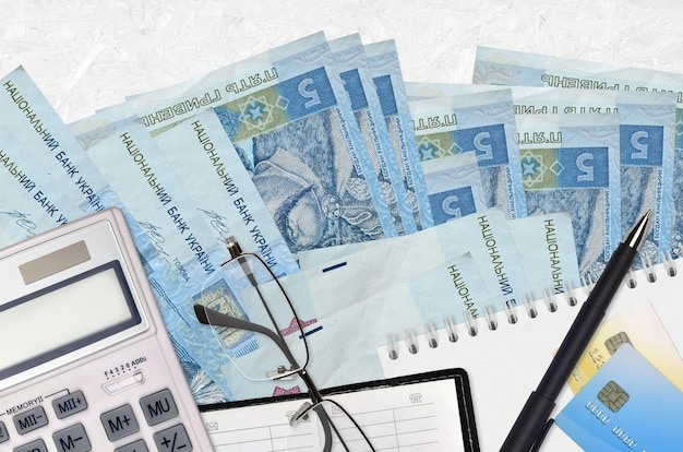 5 rachunków za ukraińskie hrywny i kalkulator z okularami i długopisem.