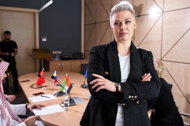 50-55 letnia biznesowa dama ze stylowymi krótkimi włosami w formalnym stroju pozuje w sali konferencyjnej podczas spotkania z międzynarodową grupą polityków siedzących przy biurku w tle. portret
