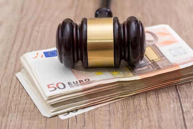 50 euro z młotkiem na drewnianym biurku