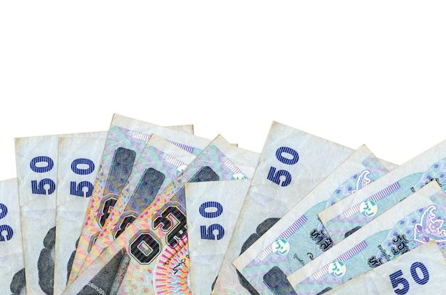50 rachunków bahtów tajskich leży w dolnej części ekranu na białym tle na białej ścianie z miejsca na kopię.