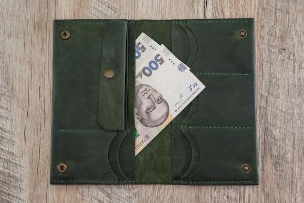 500 hrywien w otwartym portfelu na drewnianym stole. koncepcja finansowa.