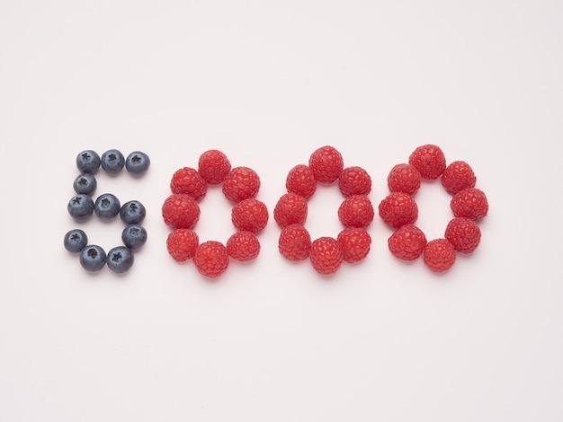 5000 pięć tysięcy sztuk wykonanych z malin i jagód na różowym tle