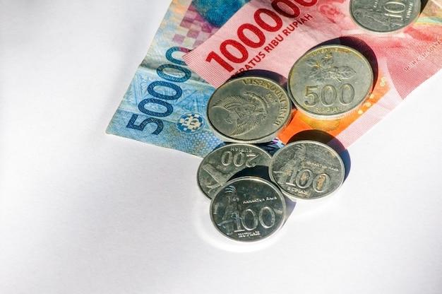 50000 i 100000 rupia indonezyjska waluta i niektóre stare monety rupii, na białym tle. pojęcie oszczędzania i inflacji