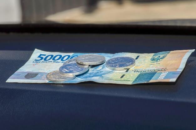 50000 waluty indonezyjskiej rupii i kilka monet rupii na ciemnym stole