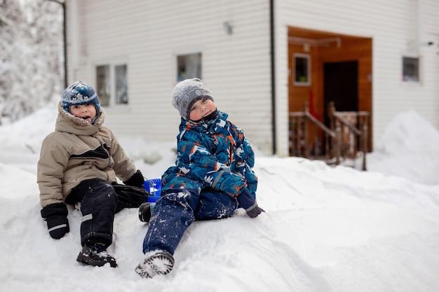 56-letni chłopcy siedzący na zjeżdżalni w zimowy dzień wiejski dom na backgrownd