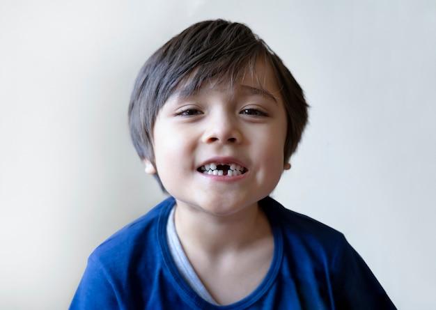 6-7-letni chłopiec uśmiecha się i pokazuje brakujące zęby. słodkie dziecko straciło pierwszy ząb mleczny.