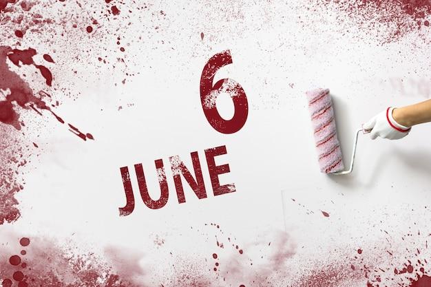 6 czerwca. dzień 6 miesiąca, data kalendarzowa. ręka trzyma wałek z czerwoną farbą i pisze datę w kalendarzu na białym tle. miesiąc letni, koncepcja dnia roku.