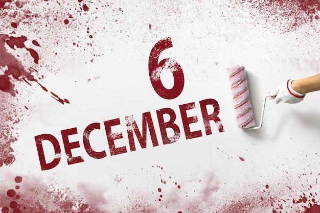 6 grudnia. dzień 6 miesiąca, data kalendarzowa. ręka trzyma wałek z czerwoną farbą i pisze datę w kalendarzu na białym tle. miesiąc zimowy, koncepcja dnia roku.