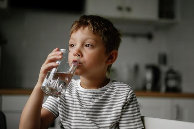 6-letni chłopiec pijący wodę ze szkła siedzący przy stole i patrzący na bok