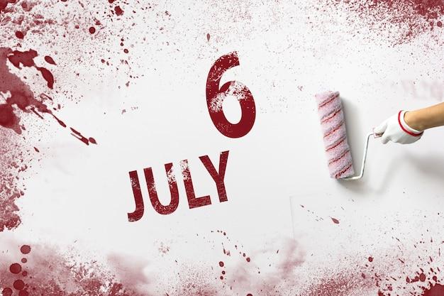 6 lipca. dzień 6 miesiąca, data kalendarzowa. ręka trzyma wałek z czerwoną farbą i pisze datę w kalendarzu na białym tle. miesiąc letni, koncepcja dnia roku.