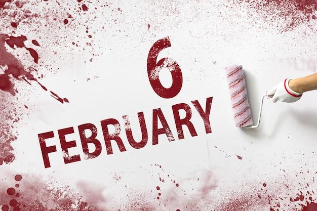 6 lutego. dzień 6 miesiąca, data kalendarzowa. ręka trzyma wałek z czerwoną farbą i pisze datę w kalendarzu na białym tle. miesiąc zimowy, koncepcja dnia roku.
