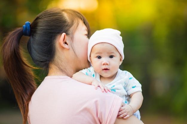 6 miesięcy słodkie dziecko czuje się szczęśliwe i uśmiecha się z matką