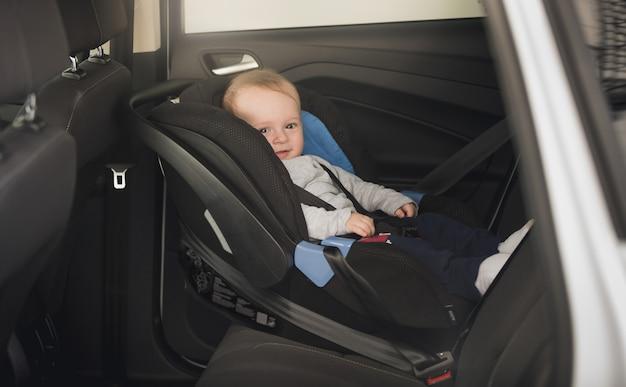 6-miesięczny chłopiec siedzi w dziecięcym foteliku samochodowym