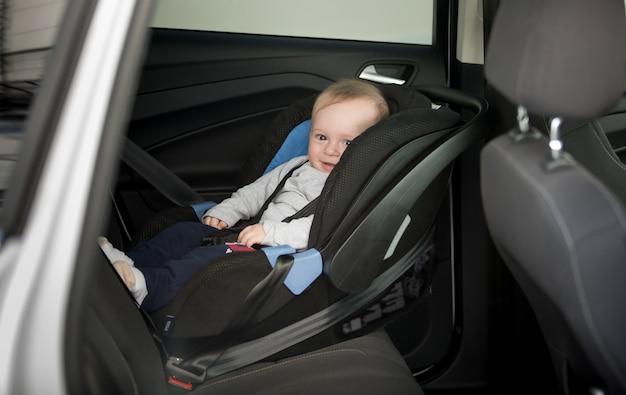 6-miesięczny chłopiec siedzi w foteliku dziecięcym w samochodzie