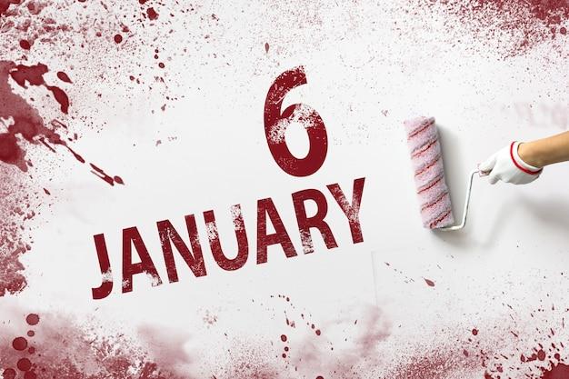 6 stycznia. dzień 6 miesiąca, data kalendarzowa. ręka trzyma wałek z czerwoną farbą i pisze datę w kalendarzu na białym tle. miesiąc zimowy, koncepcja dnia roku.
